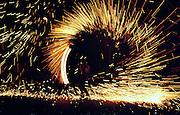 """..Eine Straßenkünstlerin schleudert eine Feuerkette. Eine feuershow im Rahmen des """"Grenzcamps"""" 1999. An Artist rotate a chain with a burning bowl at the end."""