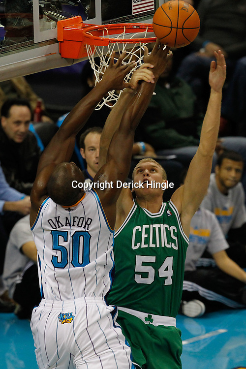 December 28, 2011; New Orleans, LA, USA; New Orleans Hornets center Emeka Okafor (50) is fouled by Boston Celtics center Greg Stiemsma (54) during the first quarter of a game at the New Orleans Arena.   Mandatory Credit: Derick E. Hingle-US PRESSWIRE