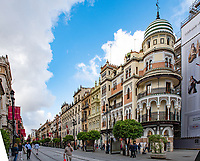Av de la constitucion in Seville features colorful architecture, interesting buildings and is a main throughway for the public train system of the city.