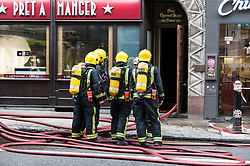 © Licensed to London News Pictures. 11/11/2015. A fire burns in a building on Fleet Street, to the left of the Goldman Sachs building.  A sign labelled Mary Queen of Scots house stands above the doorway.  Several fire engines, their crew and police are in attendance.  At present the cause is unknown. Photo credit : Stephen Chung/LNP