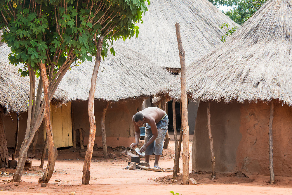 Zambian male bent over and cooking over campfire next to mud huts in village, Mukuni Village, Zambia