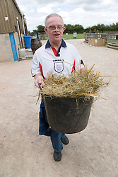 Man with learning disabilities helping to muck out a stable on a trip to an animal centre,
