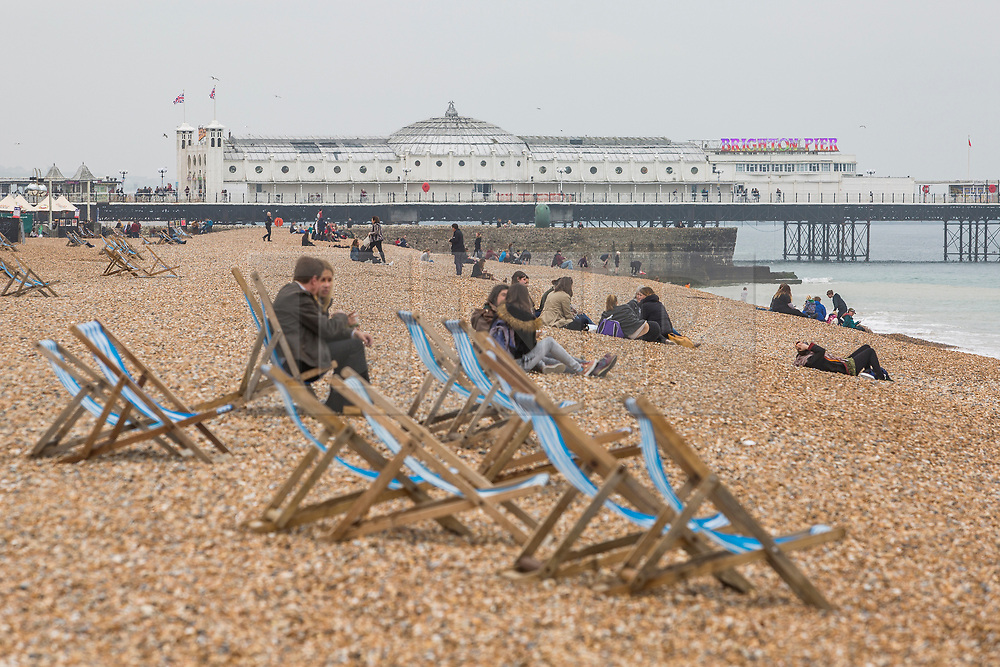 © Licensed to London News Pictures. 14/04/2018. Brighton, UK. only a handful of people can be seen on the beach in Brighton and Hove as cold and grey weather is hitting the seaside resort. Photo credit: Hugo Michiels/LNP