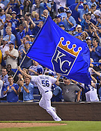 Sports Illustrated - Kansas City Royals pitcher Greg Holland (56) carries the Royals flag and celebrates with fans after a walk off win over the Oakland Athletics in the 2014 American League Wild Card playoff baseball game at Kauffman Stadium.