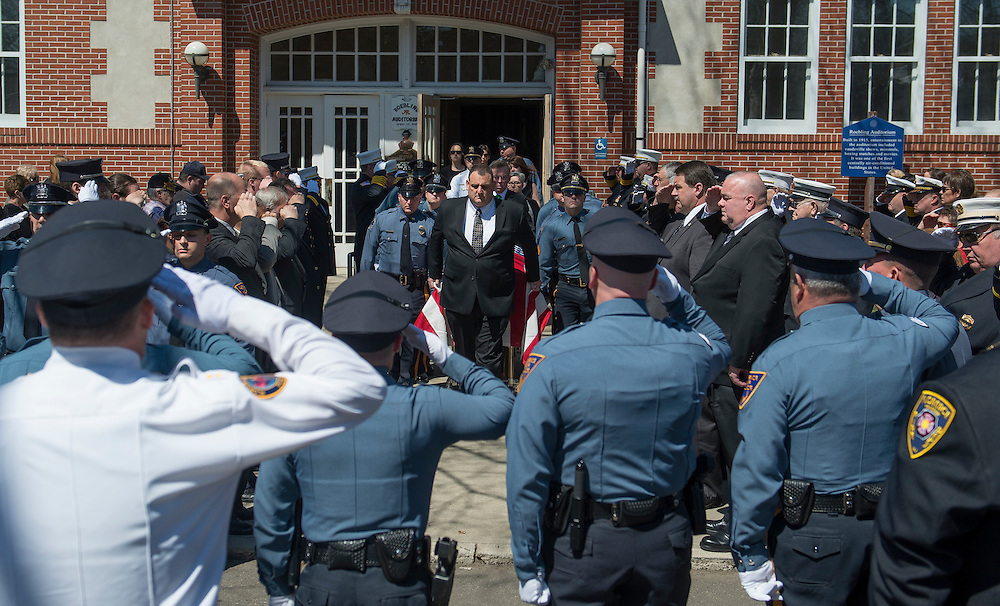 Member of the Florence Police and Fire Departments salute as an honor guard escorts the casket during the funeral for Police Chief Al Scully, Thursday, April 10, 2014 (PHOTO Bryan Woolston / @woolstonphoto)