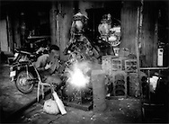 Welding in a streetfront shop in central Phnom Penh, Cambodia.  Most Khmers still exist on commerce on a very local level.