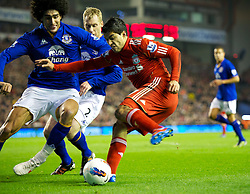 LIVERPOOL, ENGLAND - Tuesday, March 13, 2012: Liverpool's Luis Alberto Suarez Diaz in action against Everton's Marouane Fellaini and Tony Hibbert during the Premiership match at Anfield. (Pic by David Rawcliffe/Propaganda)