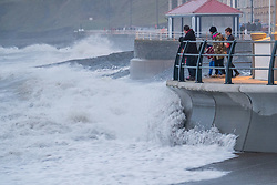 © London News Pictures. 30/12/2017. Aberystwyth, UK.  People on the seafront in Aberystwyth get an early preview of the stormy weather that is due to strike the UK  as Storm Dylan brings stormy seas and waves  to hit west Wales. Winds  are picking up and are predicted to reach up to 80mph in some areas on New Years Day, with  widespread heavy rain causing local flooding and disruption to travel. The southern areas of the UK will, however, be unusually mild, with temperatures reaching 13ºc in the south east. Photo credit: Keith Morris/LNP