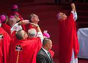 Flanked by a Salvadoran presidential security agent, priests turn their cameras to the sky hoping to see a sign from the heavens. Catholic priests from around the world  arrived at Plaza Salvador del Mundo ( Savior of the World) as El Salvador celebrated a ceremony and mass announcing the beatification of Archbishop Oscar Romero. The Archbishop was slain at the alter of his Church of the Divine Providence by a right wing gunman in 1980. Oscar Arnulfo Romero y Galdamez became the fourth Archbishop of San Salvador, succeeding Luis Chavez, and spoke out against poverty, social injustice, assassinations and torture. Romero was assassinated while offering Mass on March 24, 1980.