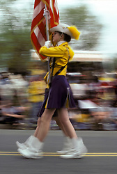 Americana Color guard of high school marching band  marches in small town holiday celebration parade.