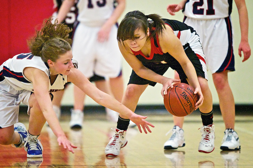 Lakeside High's Brianna Louie pulls the ball away from the grasp of Lexi Turkenburg from Coeur d'Alene Charter Academy during the first half of Tuesday's game at Holy Family Catholic School in Coeur d'Alene.