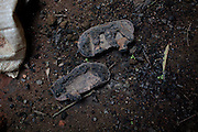 Burnt shoes once belonging to a young child are left inside a destroyed home in Kakuruk village, Gashish district, in the local government of Barkin Ladi, near Jos, Plateau State, Nigeria. The village, inhabited by Christians from the Berom tribe, has received various attacks by neighbouring Muslim Fulani - a nomadic cattle-herder tribe non-indigenous to Plateau - with the last one on 7th July, 2012, when more than 30 houses were demolished and 8 Christian villagers killed.