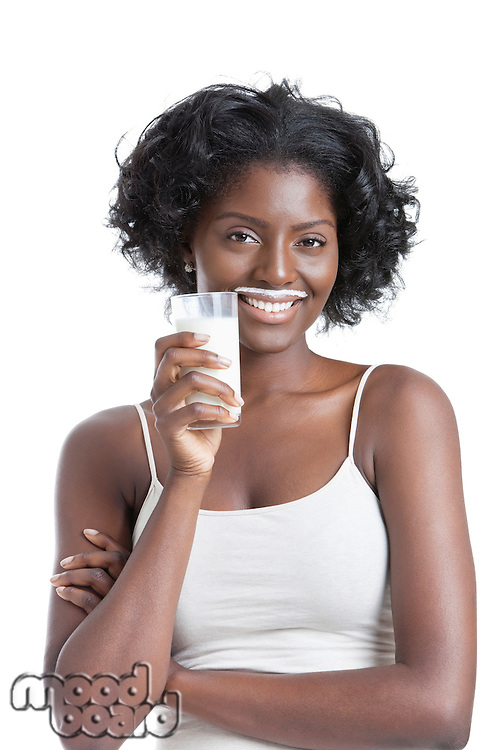 Portrait of happy young woman with milk moustache holding glass of milk