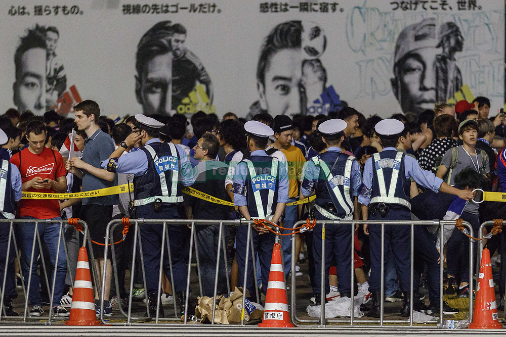 June 29, 2018 - Tokyo, Japan - Tokyo Metropolitan Police restraints Japanese soccer fans access to Shibuya's famous scramble after their team advanced to the second round of World Cup in Tokyo, Japan. Japan's Soccer National Team. Japan sealed their position to the second round of the FIFA World Cup despite losing to Poland 1-0 in Volgograd Arena in Volgograd, Russia. Soccer fans who watched the game in Tokyo gathered in Shibuya's famous scramble crossing to celebrate, the Tokyo Metropolitan Police were on hand to control access. (Credit Image: © Rodrigo Reyes Marin/via ZUMA Wire via ZUMA Wire)