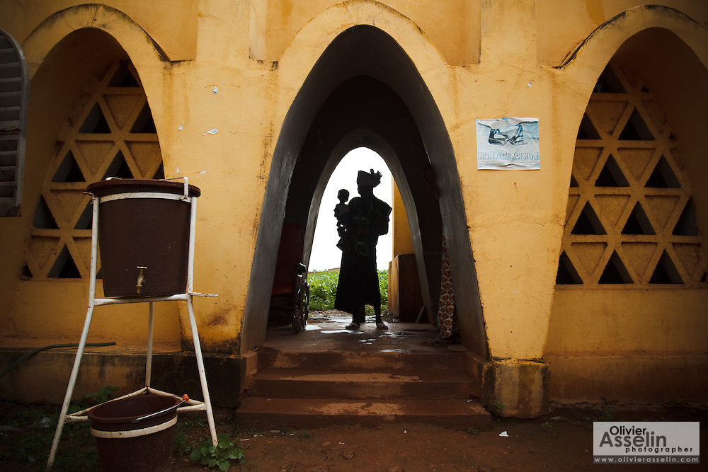 A woman holding her child stands in a doorway at the Kita reference health center in the town of Kita, Mali on Sunday August 29, 2010..