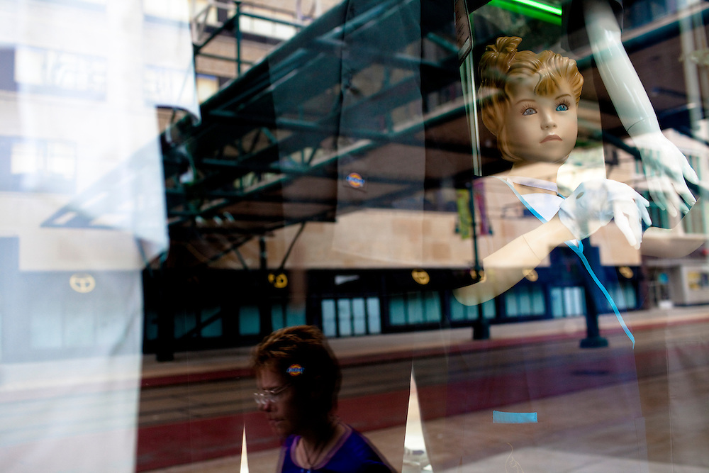A woman walking down Main Street is reflected in a store window in Buffalo, NY, on Wednesday, July 29, 2009.