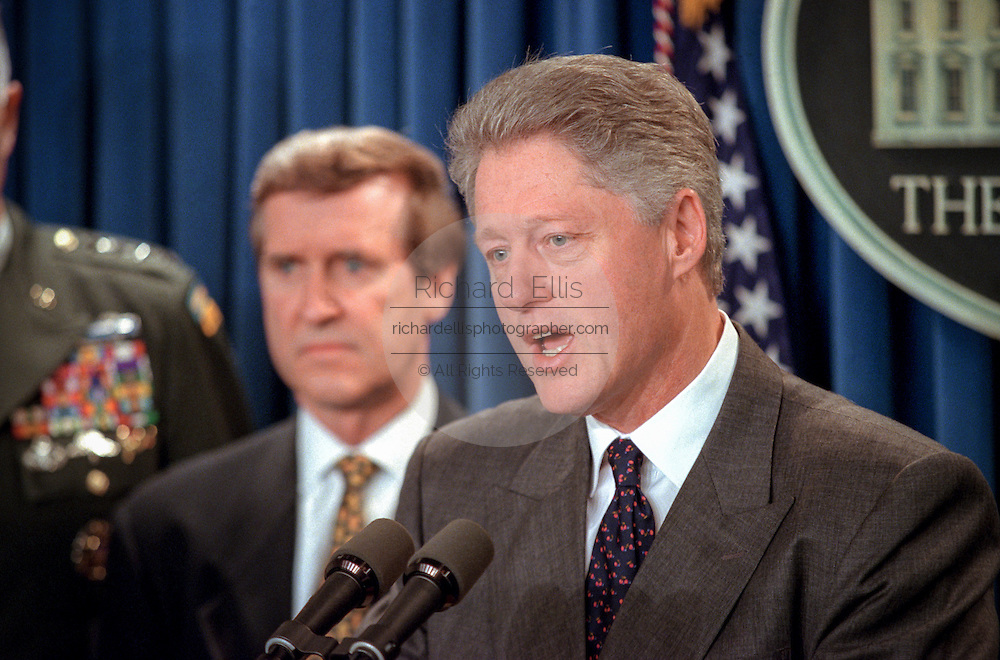 US President Bill Clinton makes a statement in the Briefing Room of the White House November 15, 1998 in Washington, DC. Clinton announced that he called off airstrikes on Iraq after Saddam Hussein agreed to allow the UN to resume weapon inspections. Standing with Clinton are Secretary of Defense William Cohen.