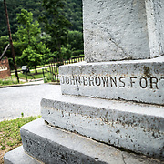 The John Brown Monument in Harpers Ferry, West Virginia. In the background at left is John Brown's Fort, which was relocated from where the monument now stands. On October 17, 1859, Brown led an attack on Harpers Ferry to launch a war against slavery.