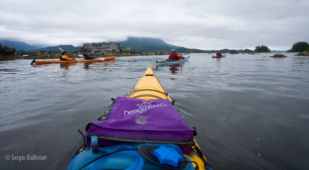 Sea kayakers enjoy the calm waters of Barkley Sound whle paddling in the Broken group Islands on Vancouver Island, BC, Canada.