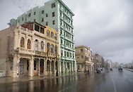 Weathered buildings along the Malecon (sea wall) through rainy windshield, Havana, Cuba