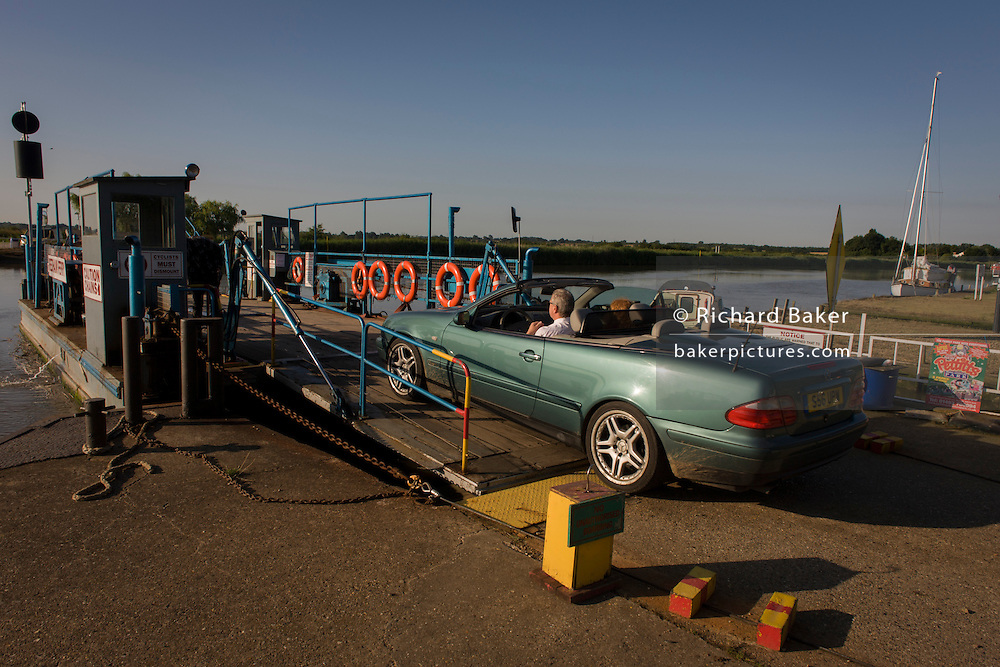 Car and passengers boarding the chain ferry crossing the River Yare in Reedham on the Norfolk Broads.
