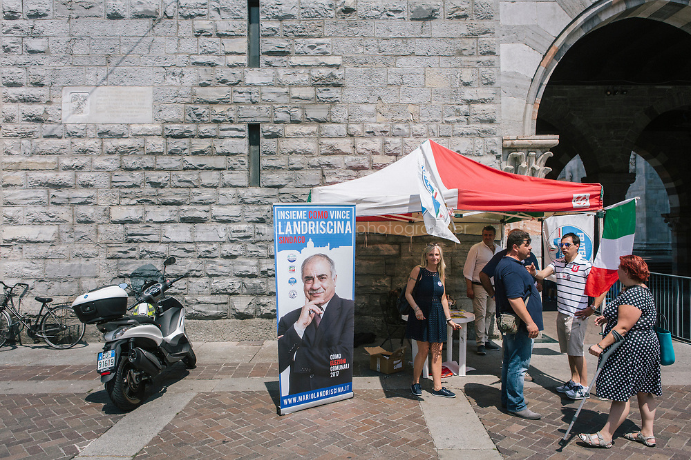 COMO, ITALY - 21 JUNE 2017: Residents of Como gather at a gazebo at Mario Landriscina's rally,  the leading candidate for mayor of Como after the first round of voting to replace the left-leaning mayor, here at the Broletto, a medieval building next to the Cathedral in Como, Italy, on June 21st 2017. Mr Landriscina wants to close the reception centers.<br /> <br /> Residents of Como are worried that funds redirected to migrants deprived the town&rsquo;s handicapped of services and complained that any protest prompted accusations of racism.<br /> <br /> Throughout Italy, run-off mayoral elections on Sunday will be considered bellwethers for upcoming national elections and immigration has again emerged as a burning issue.<br /> <br /> Italy has registered more than 70,000 migrants this year, 27 percent more than it did by this time in 2016, when a record 181,000 migrants arrived. Waves of migrants continue to make the perilous, and often fatal, crossing to southern Italy from Africa, South Asia and the Middle East, seeing Italy as the gateway to Europe.<br /> <br /> While migrants spoke of their appreciation of Italy&rsquo;s humanitarian efforts to save them from the Mediterranean Sea, they also expressed exhaustion with the country&rsquo;s intricate web of permits and papers and European rules that required them to stay in the country that first documented them.
