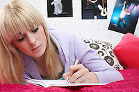 Teenage girl (16-17) lying on bed writing diary