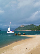 A sailboat passes by the Three Mermaids statues on Daydream Island; Whitsunday Islands, QLD, Australia