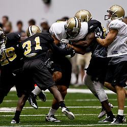 July 31, 2010; Metairie, LA, USA; New Orleans Saints defenders combine to tackle tight end Jimmy Graham (80) during a training camp practice at the New Orleans Saints indoor practice facility. Mandatory Credit: Derick E. Hingle