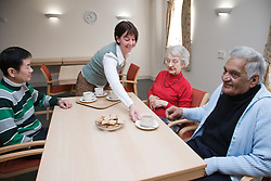 Group of older people having tea in a care home,