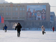 Passersby on Lenin Square in the city center of Yakutsk. Yakutsk was founded in 1632 and celebrated 2007 the 375th anniversary - billboard announcing the celebration. Yakutsk is a city in the Russian Far East, located about 4 degrees (450 km) below the Arctic Circle. It is the capital of the Sakha (Yakutia) Republic (formerly the Yakut Autonomous Soviet Socialist Republic), Russia and a major port on the Lena River. Yakutsk is one of the coldest cities on earth, with winter temperatures averaging -40.9 degrees Celsius.