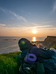 Backpacker  Sitting on Cliff Admiring Ocean View at Sunset