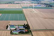 Solar panels on farm building and wind turbines.