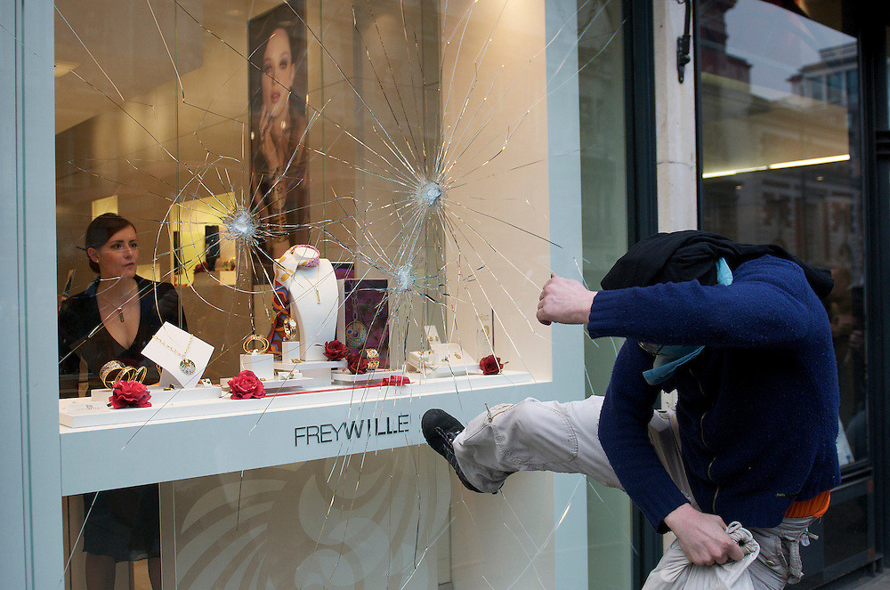 A protester smashes a shop window in <br /> Piccadilly in central London as the shopkeepr looks on.