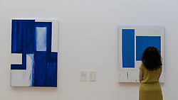 "© Licensed to London News Pictures. 07/06/2016. London, UK.   A visitor views (L to R) ""Ming"" and Blue and White Squares"", by the American artist Mary Heilmann, which are previewed ahead of her first major UK exhibition, ""Looking at Pictures"", at the Whitechapel Gallery.  The exhibition spans the artist's five decade career, from her early geometric paintings made in the 1970s to her recent shaped canvases in day-glo colours.  The show features approximately 45 paintings as well as a selection of ceramics, chairs and works on paper, many of which have never been exhibited.  Photo credit : Stephen Chung/LNP"