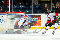 KELOWNA, BC - NOVEMBER 8:  Cole Clayton #34 tries to get control of the puck as Mads Søgaard #30 of the Medicine Hat Tigers defends the net against the Kelowna Rockets at Prospera Place on November 8, 2019 in Kelowna, Canada. (Photo by Marissa Baecker/Shoot the Breeze)