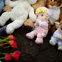 A memorial of flowers and cuddly toys soiled by rain and mud is arranged at an intersection in Newtown, CT, on December 17, 2012, 3 days after a mass shooting of 20 children and 7 adults at Sandy Hook Elementary School.