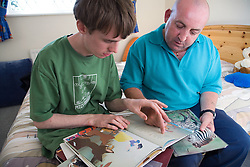 Teenage boy with Autism learning to read with help of his carer,