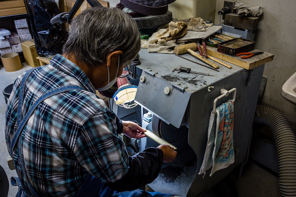 One of the workers at the sword shop makes a tsuka, or sword handle piece, from a piece of wood.