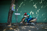 A vietnamese woman takes a nap on her motorbike between Vung Tau and HCMC, Vietnam, Southeast Asia
