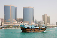 Dubai UAE A dhow old wooden sailing vessel cruises down Dubai Creek in front of the Rolex Tower.