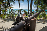 A WWII Japanese artillery gun sits in the trees, as tourists walk the white sand beaches on Managaha Island in Saipan's lagoon. Saipan was the site of a fierce major WWII battle between the Japanese and US, mainly Marines. 5000 Marines died winning control of the island, a key to Japan's control of the Pacific.