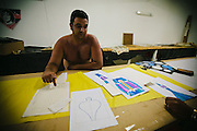 """En Rio de Janeiro, hay cientos de miles de aficionados a los globos. Sus puntos de encuentro y trabajo se llaman """"bancadas"""" -las largas encimeras de madera donde corytan el papel y montan los globos."""