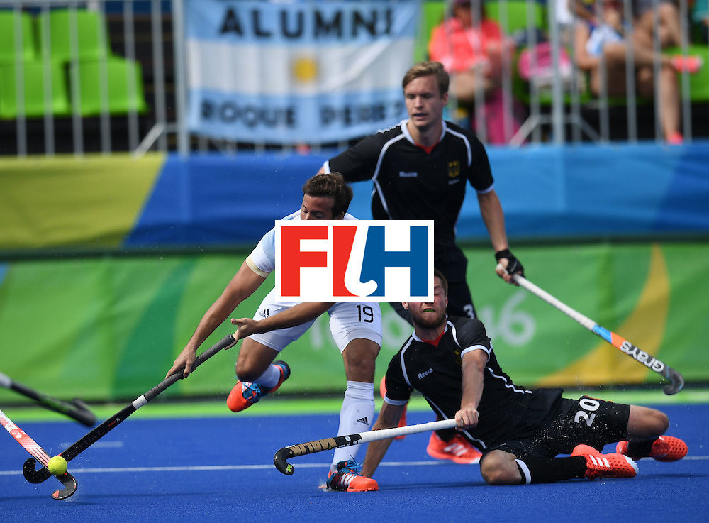 Argentina's Juan Saladino (L) fights for the ball with Germany's Martin Zwicker during the men's field hockey Argentina vs Germany match of the Rio 2016 Olympics Games at the Olympic Hockey Centre in Rio de Janeiro on August, 11 2016. / AFP / MANAN VATSYAYANA        (Photo credit should read MANAN VATSYAYANA/AFP/Getty Images)