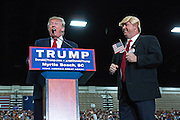 Republican presidential candidate billionaire Donald Trump reacts as he brings a imitator in costume onstage during a campaign rally at the Myrtle Beach Convention Center November 24, 2015 in Myrtle Beach, South Carolina.