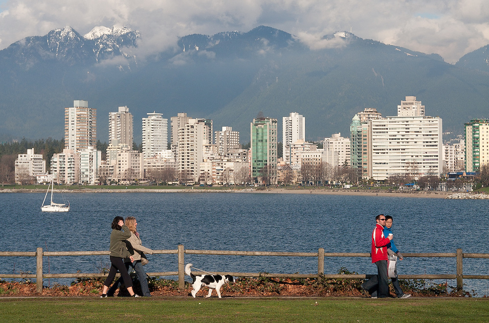 Dog walkers stroll infront of a sunny & beautiful view looking over the Burrard Inlet in Kitsilano, Vancouver. A popular area for dog walkers and joggers eager for excercise. The city of vancouver is in the background followed by a backdrop of mountains.