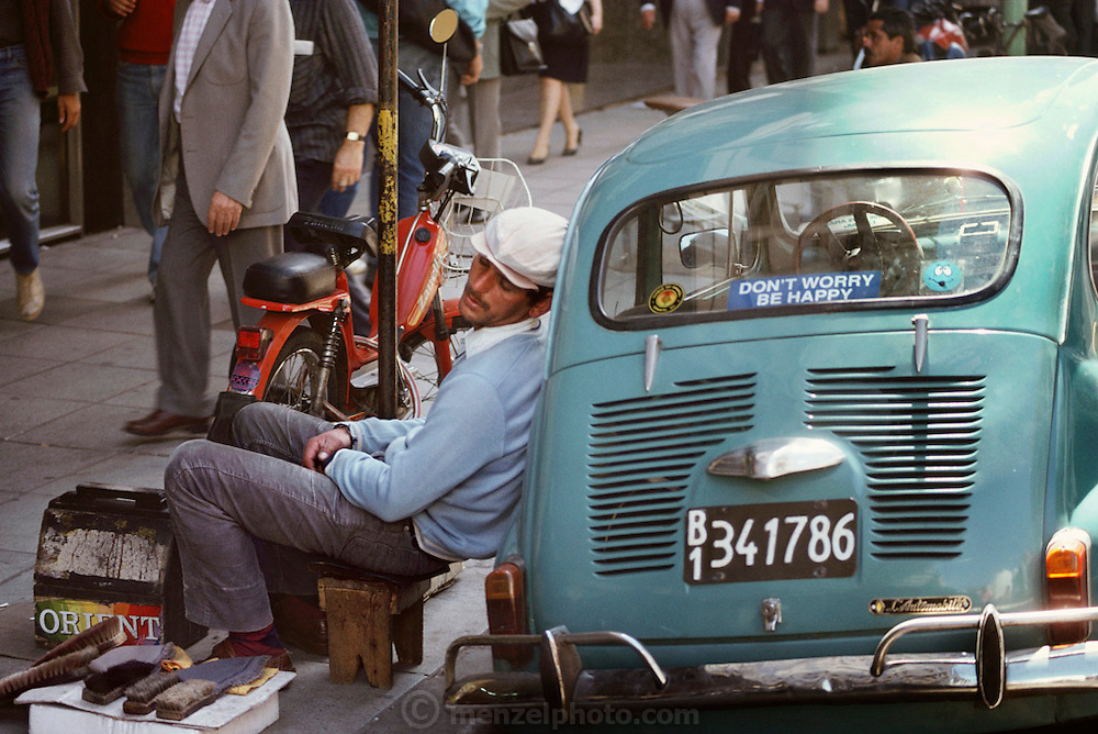 Shoeshine man napping, leaning against a car, Buenos Aires, Argentina.