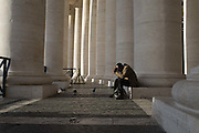 A man prays while sitting beneath large pillars at the Vatican