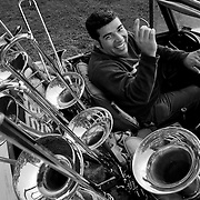 "Denis Jiron, a conservatory-trained classical and jazz trombonist, poses with his most ""indispensable objects"": his first and favorite car, a 1972 Datsun Convertible,  and his personal collection of 8 trombones of different types and ages spanning from 1932 to present. He is posing in the front yard of his family's home in Bloomington, California, on April 15, 2009. Photo by Jen Klewitz"