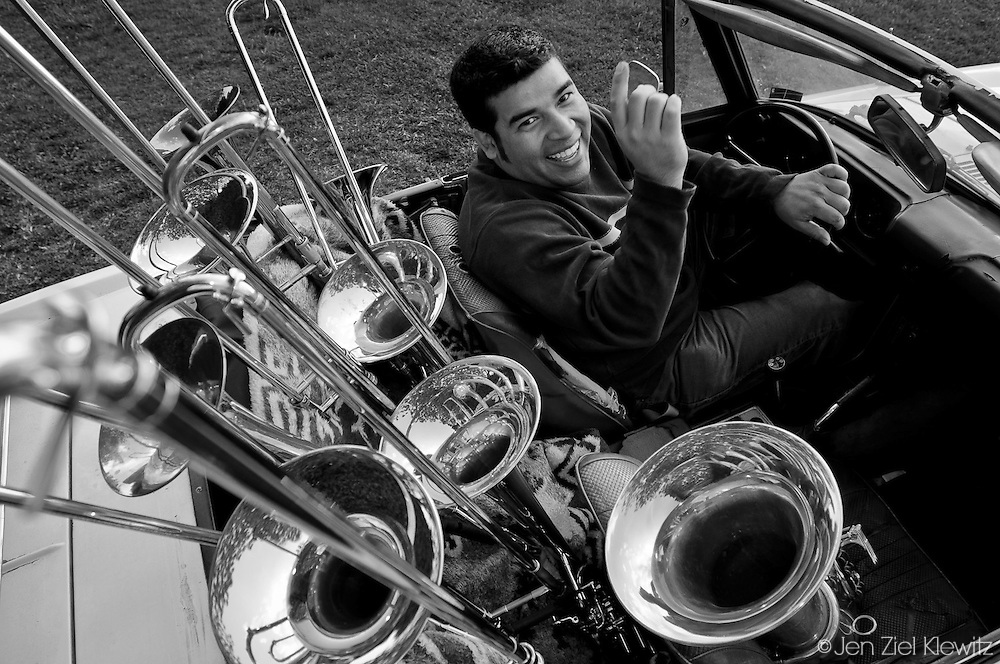 """Denis Jiron, a conservatory-trained classical and jazz trombonist, poses with his most """"indispensable objects"""": his first and favorite car, a 1972 Datsun Convertible,  and his personal collection of 8 trombones of different types and ages spanning from 1932 to present. He is posing in the front yard of his family's home in Bloomington, California, on April 15, 2009. Photo by Jen Klewitz"""